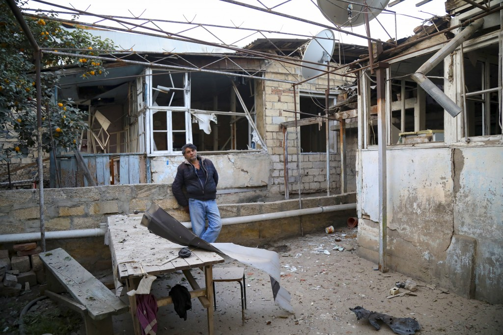 A man stands in a yard of his destroyed house in a residential area that was hit by rocket fire overnight by Armenian forces, early Saturday, Oct. 17,...