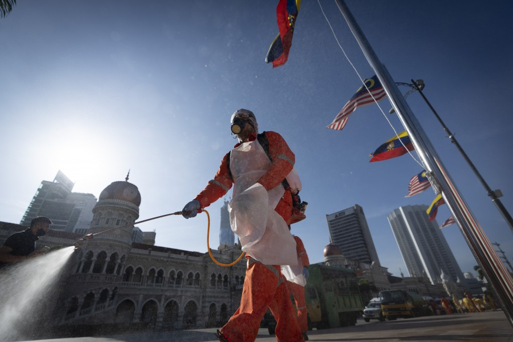 A city hall worker sprays a disinfectant at Merdeka Square, or independence square, situated in front of the Sultan Abdul Samad Building, background, ...