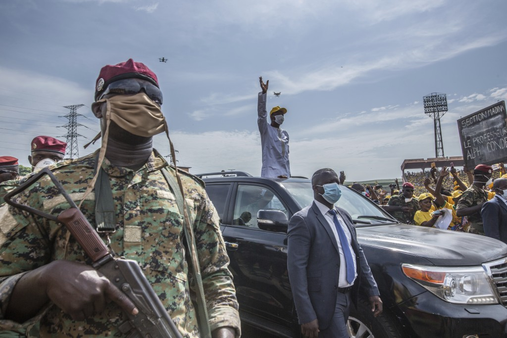 Guinean President Alpha Conde wave at supporters as he arrives at a campaign rally in Conakry, Guinea, Friday, Oct. 16, 2020. Conde is seeking a third...