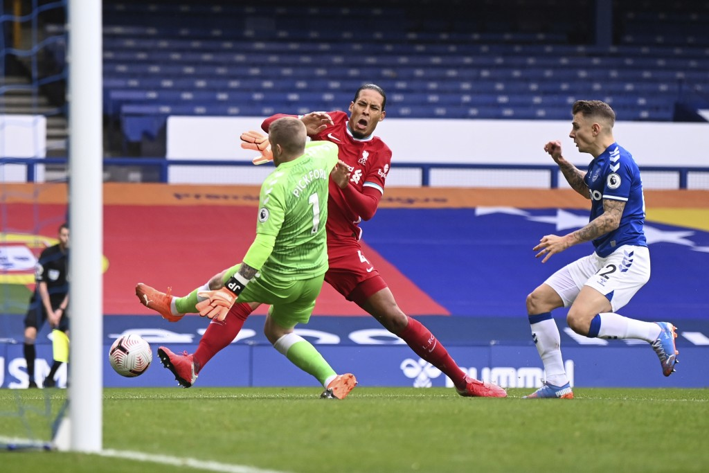 Liverpool's Virgil van Dijk, centre, is tackled and injured by Everton's goalkeeper Jordan Pickford, left, causing him to leave the match injured duri...