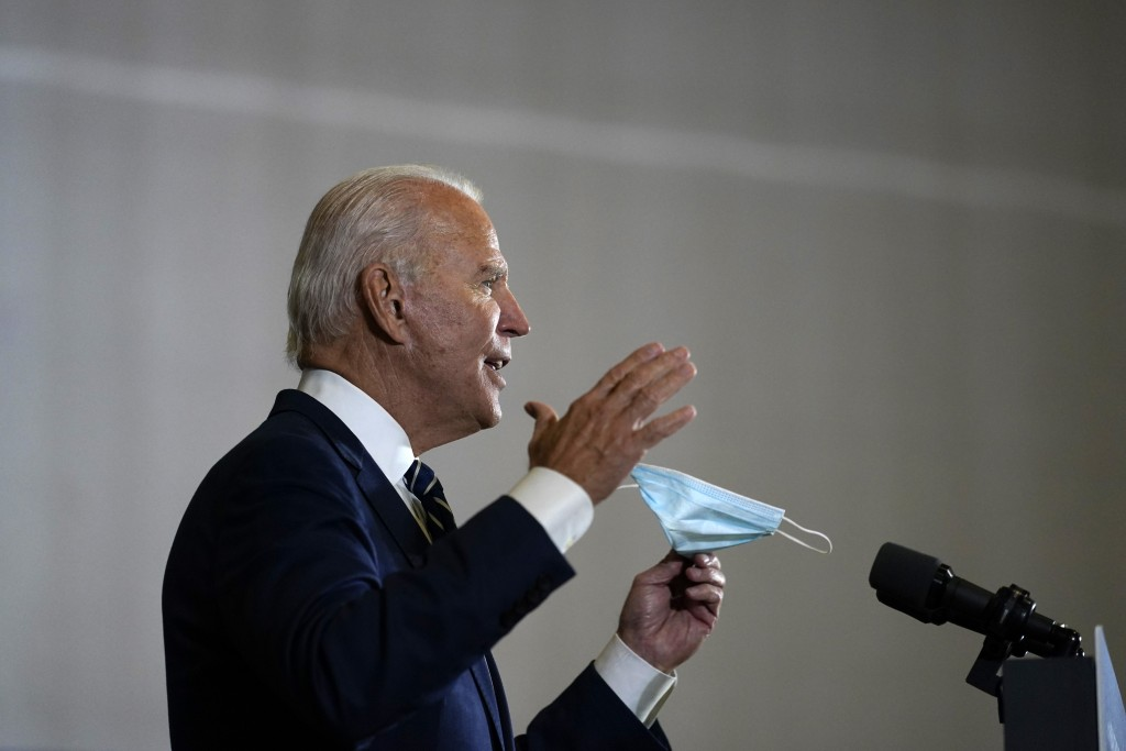 Democratic presidential candidate former Vice President Joe Biden holds a mask as he speaks at Beech Woods Recreation Center, in Southfield, Mich., Fr...