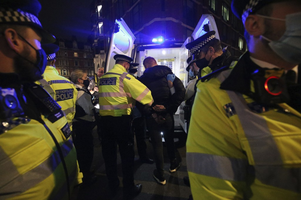 Police detain a man while dispersing a gathering in Soho on the last night before the city is put into Tier 2 restrictions to curb the spread of coron...