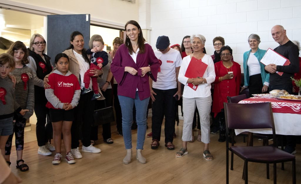 New Zealand Prime Minister Jacinda Ardern stands with her electorate workers at an event in Auckland, New Zealand, Saturday, Oct. 17, 2020. New Zealan...