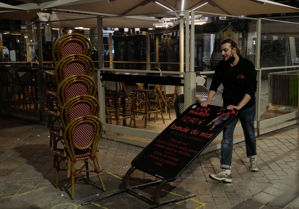 A waiter closes a bar terrace in Lille, northern France, Friday, Oct. 16, 2020. France is deploying 12,000 police officers to enforce a new curfew com...