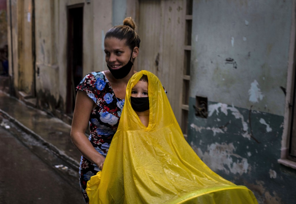 Wearing protective face masks amid the new coronavirus pandemic, a woman pushes a cart with a child wearing a raincoat during a light rain in Havana, ...