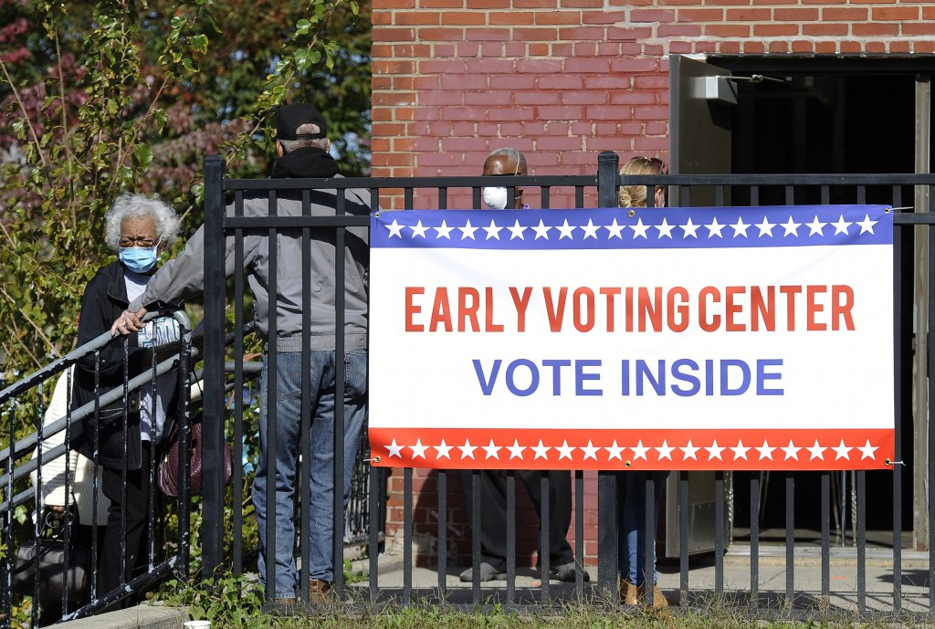FILE - In this Oct. 15, 2020, file photo, voters line up at an early voting satellite location at the Anne B. Day elementary school in Philadelphia. A...