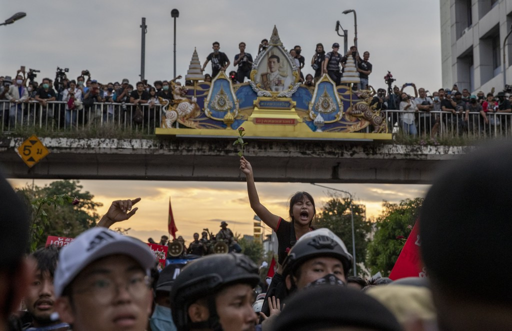 Pro-democracy protesters march past a portrait of Thai King Maha Vajiralongkorn during a rally in Bangkok, Thailand, Wednesday, Oct. 14, 2020. Thousan...