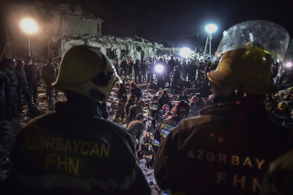 Azerbaijani soldiers and firefighters try to save survivors from destroyed houses in a residential area in Ganja, Azerbaijan's second largest city, ne...