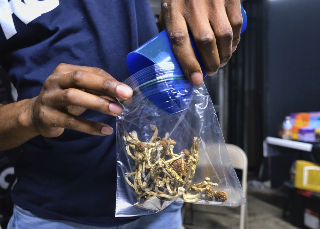FILE - In this May 24, 2019, file photo a vendor bags psilocybin mushrooms at a pop-up cannabis market in Los Angeles. Voters in Oregon in November 20...