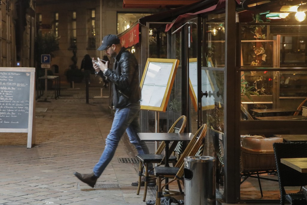A man leaves a restaurant after closing in Saint Germain-en-Laye, west of Paris, Friday, Oct. 16, 2020. France is deploying 12,000 police officers to ...