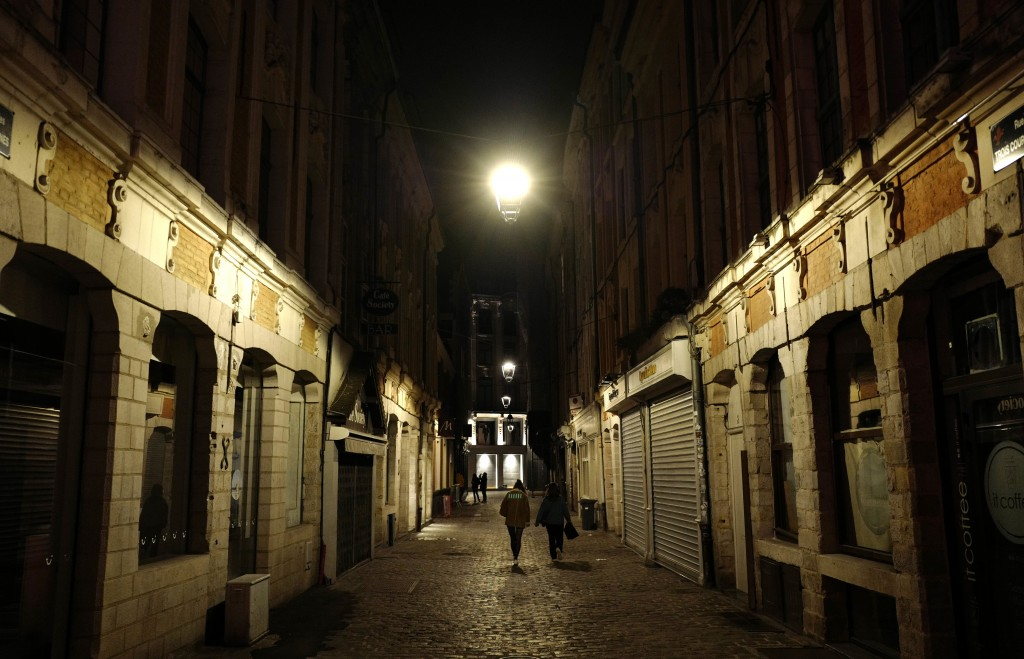 People walk in Lille, northern France, Friday, Oct. 16, 2020. France is deploying 12,000 police officers to enforce a new curfew coming into effect Fr...