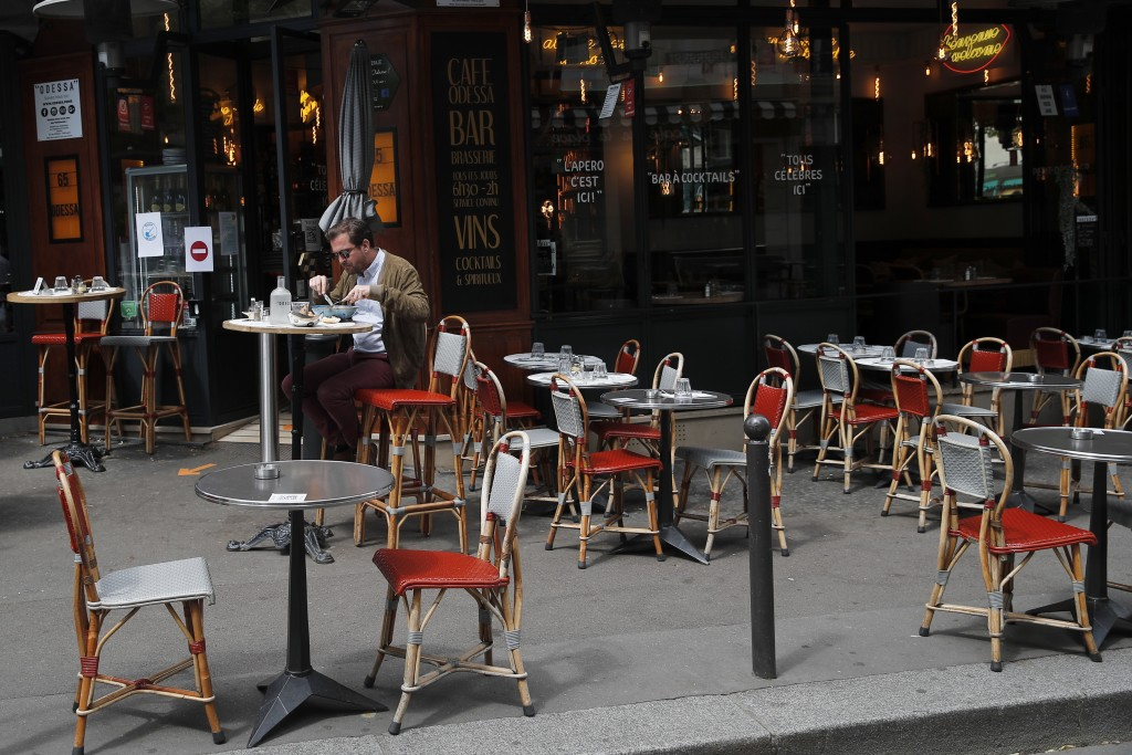 FILE - In this Monday, June 15, 2020 file photo, a man takes his lunch on a terrace at a restaurant, in Paris. Europe's economy was just catching its ...