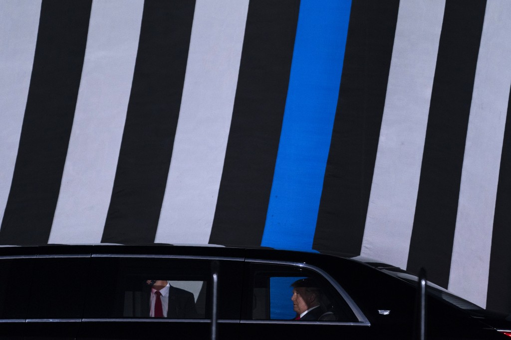 """With a """"Thin Blue Line"""" flag in the background, President Donald Trump arrives to speak to a campaign rally at Middle Georgia Regional Airport, Friday..."""