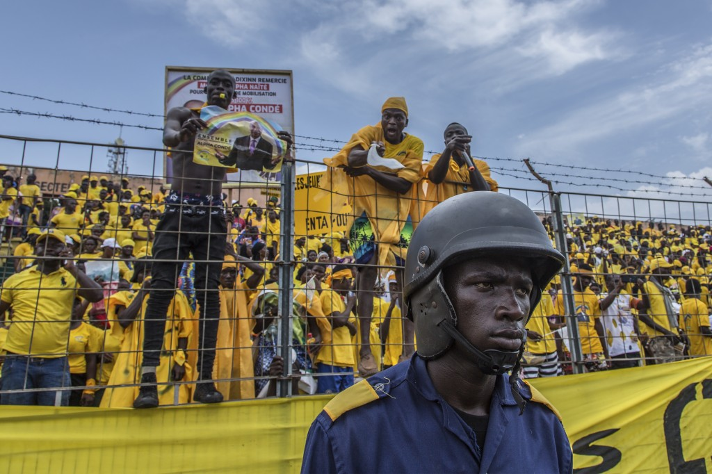 Supporters of Guinean's president candidate Alpha Conde cheers his arrival at a campaign rally in Conakry, Guinea, Friday, Oct. 16, 2020. Conde is see...