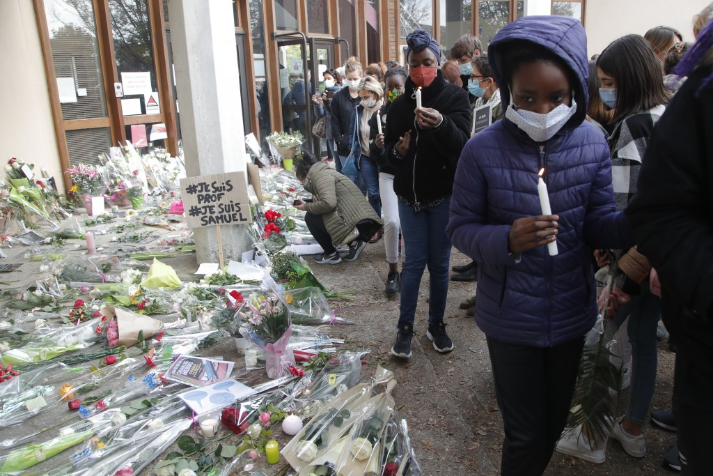 Girls light candles outside the school where a slain history teacher was working, Saturday, Oct. 17, 2020 in Conflans-Sainte-Honorine, northwest of Pa...