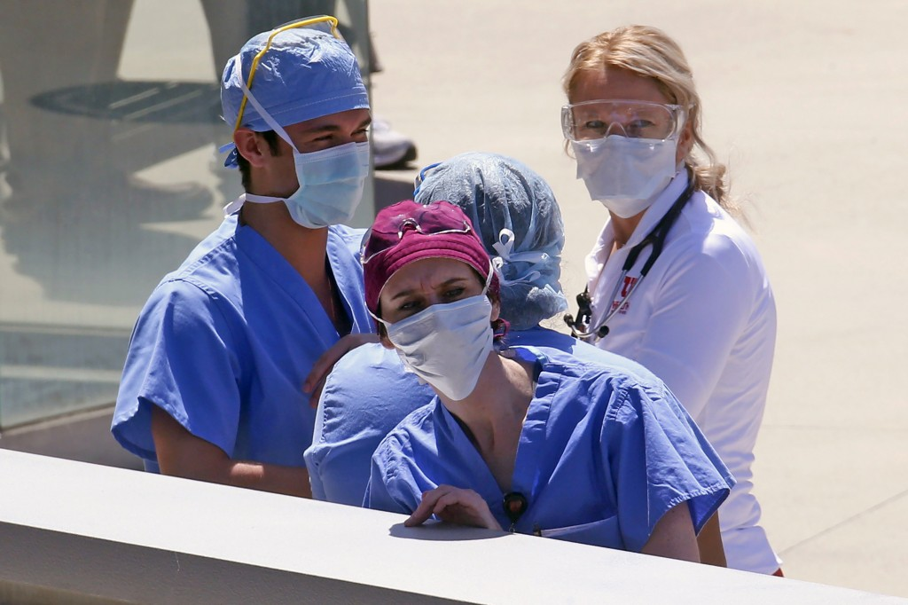 FILE - In this Thursday, April 30, 2020 file photo, Health care workers look on during a flyover at the University of Utah Hospital in Salt Lake City....