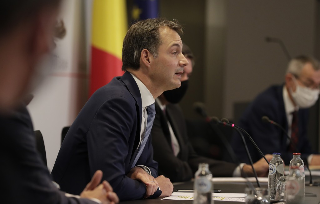 Belgium's Prime Minister Alexander De Croo, center, speaks during a media conference, after a committee to discuss new restrictive measures regarding ...