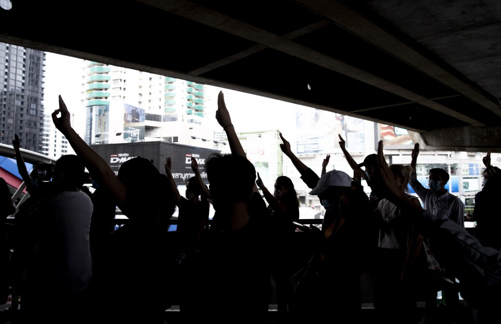 Pro-democracy protesters flash three-fingers salute against shutting down mass transport system at Ashok BTS station in Bangkok, Thailand, Saturday, O...