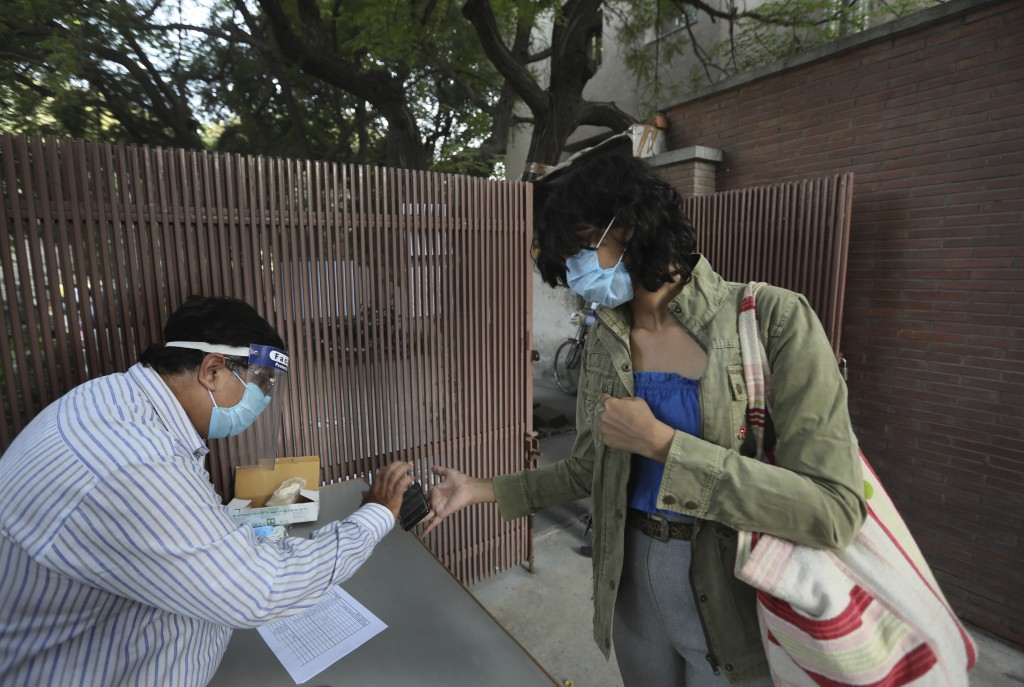 An official checks a coronavirus finder app on the mobile phone of a model before giving her entry to the Fashion Development Corporation of India (FD...