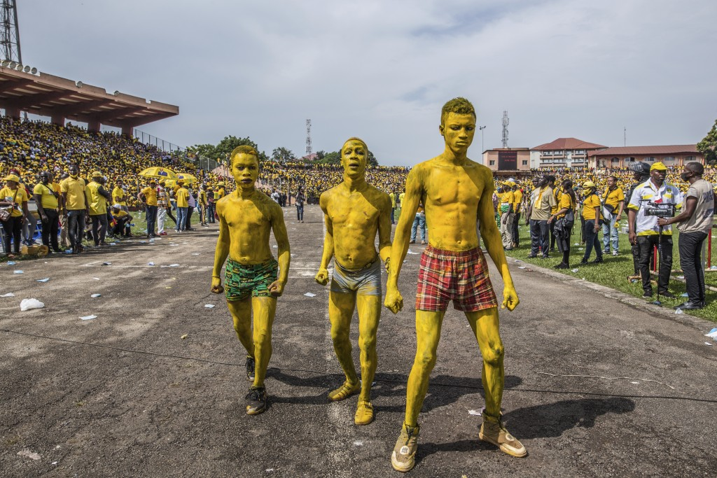 Supporters of Guinean President Alpha Conde cheers his arrival at a campaign rally in Conakry, Guinea, Friday, Oct. 16, 2020. Conde is seeking a third...