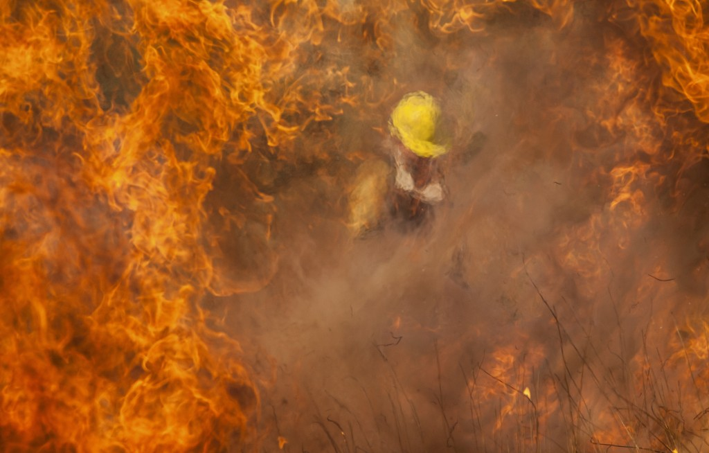A firefighter battles flames in Capilla del Monte, Cordoba, Argentina, Thursday, Oct. 15, 2020. During Wednesday night a light rain extinguished all t...