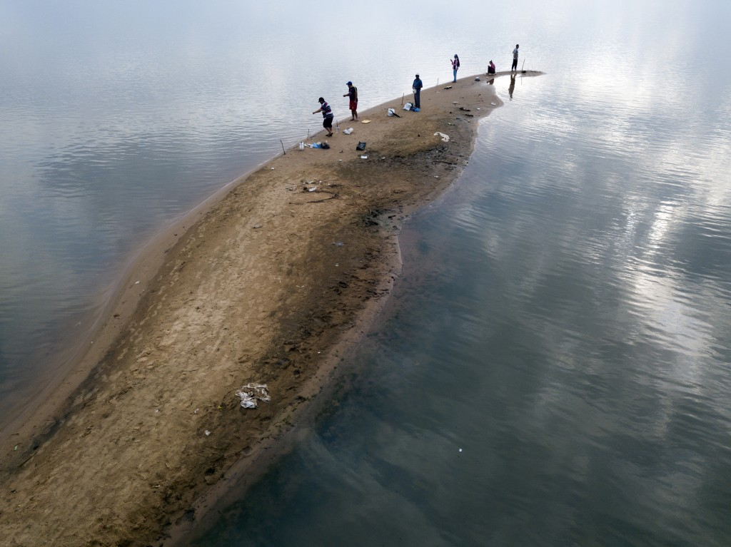 Men fish from a sand bank on the Paraguay River, taking advantage of the historical drop of water levels in San Antonio, Paraguay, on the outskirts of...