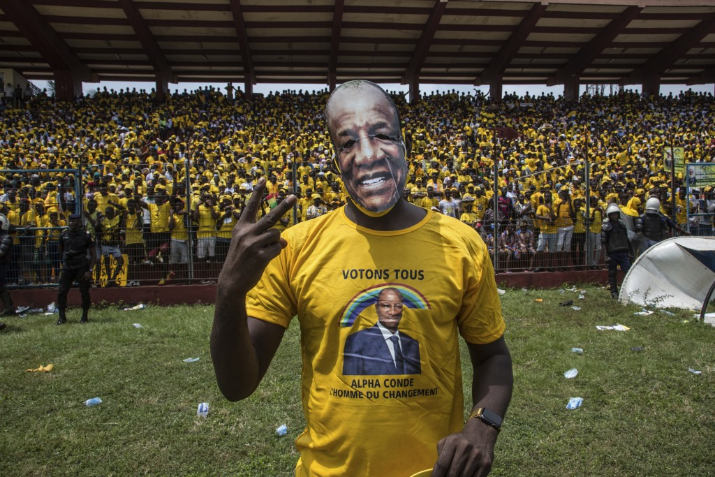 Supporters of Guinean President Alpha Conde cheer his arrival at a campaign rally in Conakry, Guinea, Friday, Oct. 16, 2020. Conde is seeking a third ...