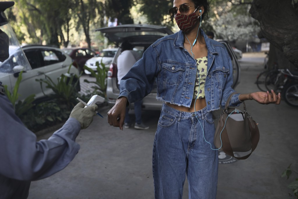 A man checks the temperature of a model as she enters the office of the Fashion Development Corporation of India (FDCI) in preparation for the Lotus m...