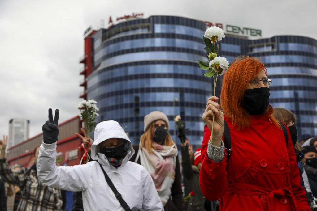 Belarusian women wearing face masks to protect agains coronavirus attend an opposition rally to protest the official presidential election results in ...
