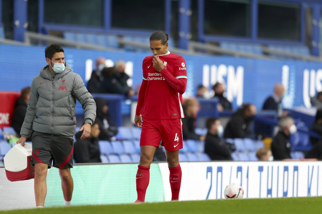 Liverpool's Virgil van Dijk leaves the match with an injury during the English Premier League soccer match between Everton and Liverpool at Goodison P...