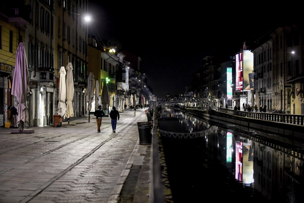 FILE - In this Sunday, March 8, 2020 file photo, the Navigli district of Milan, one of Milan's night life areas, is almost deserted after most bars we...