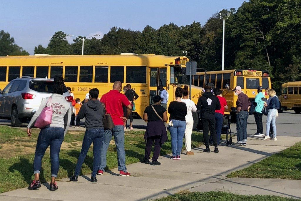 In this Thursday, Oct. 15, 2020, photo voters line up at Mallard Creek High School during the first day of in-person voting ahead of the Nov. 3 electi...
