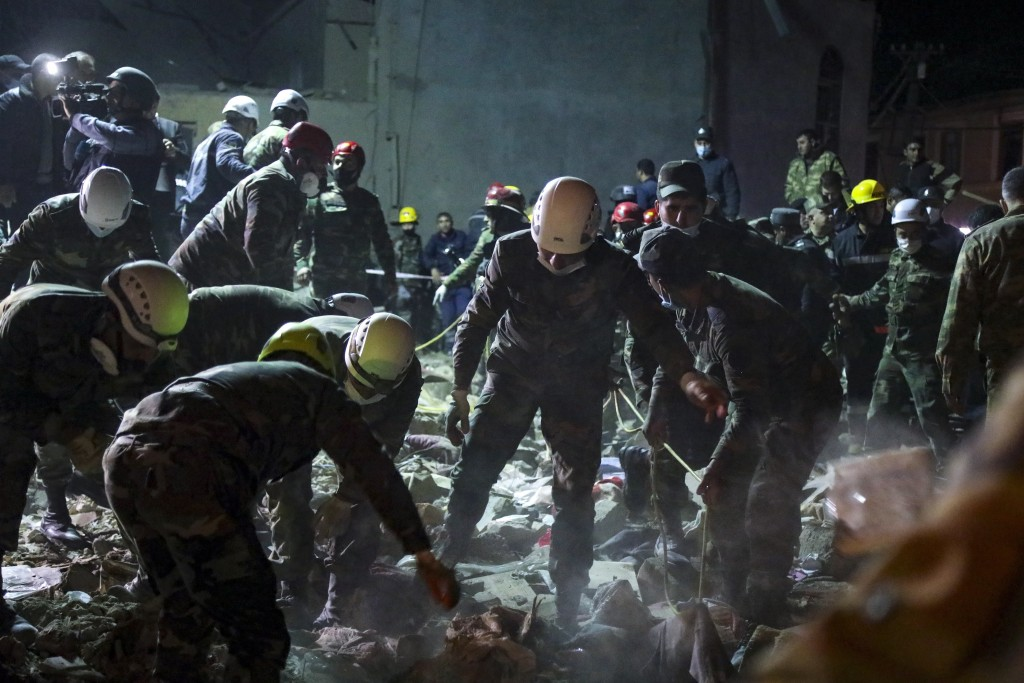 Soldiers and firefighters search for survivors in a residential area that was hit by rocket fire overnight by Armenian forces, early Saturday, Oct. 17...