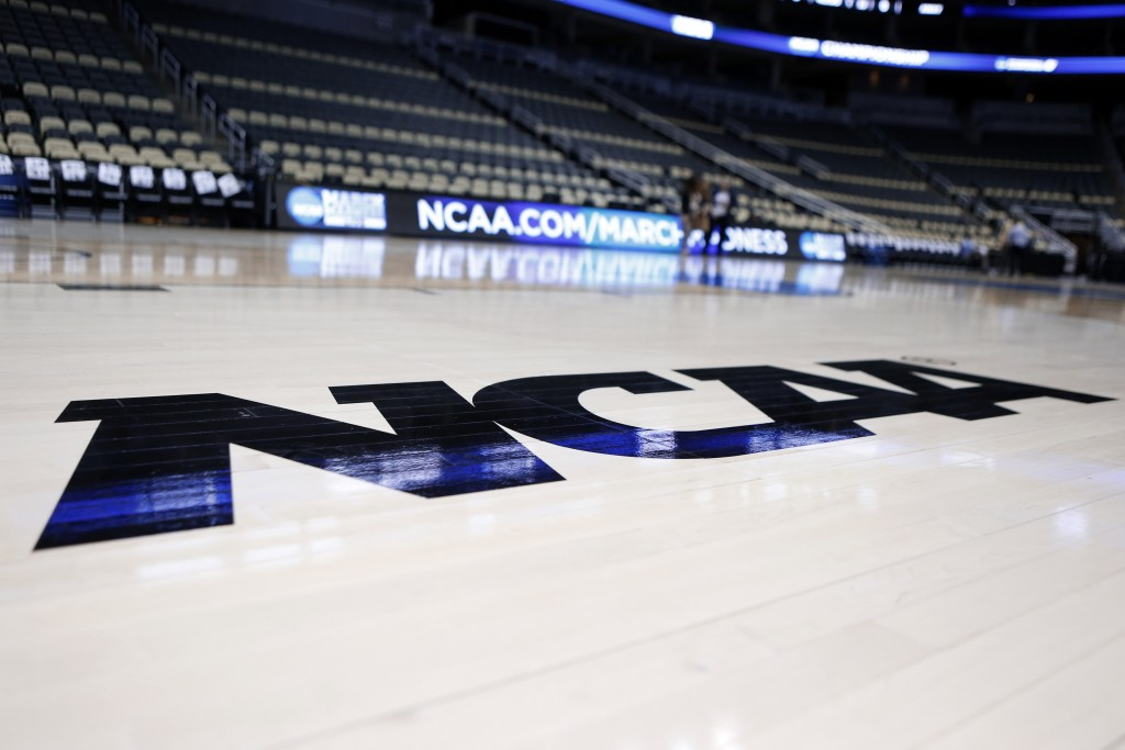 FILE - In this March 18, 2015, file photo, the NCAA logo is  displayed on the court as work continues at The Consol Energy Center in Pittsburgh. Coach...