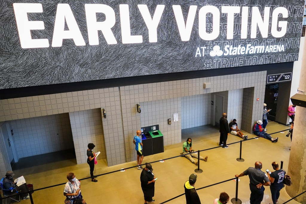 FILE - In this Oct. 12, 2020, file photo, people wait in line to vote early at the State Farm Arena in Atlanta. A surge in coronavirus cases is hittin...