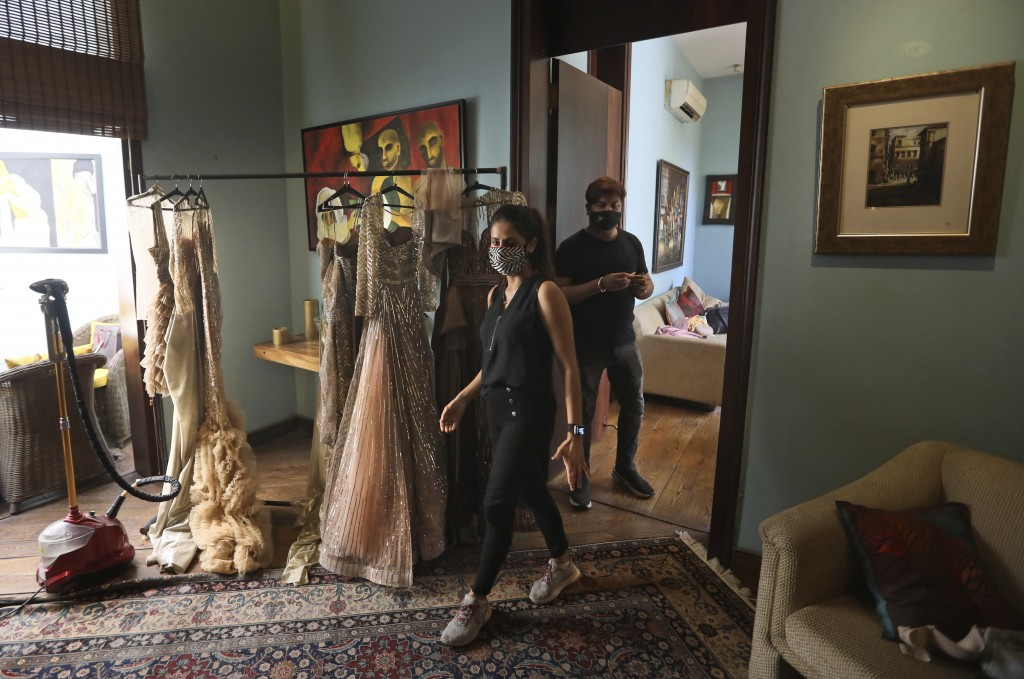 Back stage staff wearing face masks walk past a room where outfits are hung for a shoot ahead of the Lotus Make-up India Fashion Week, in the farmhous...