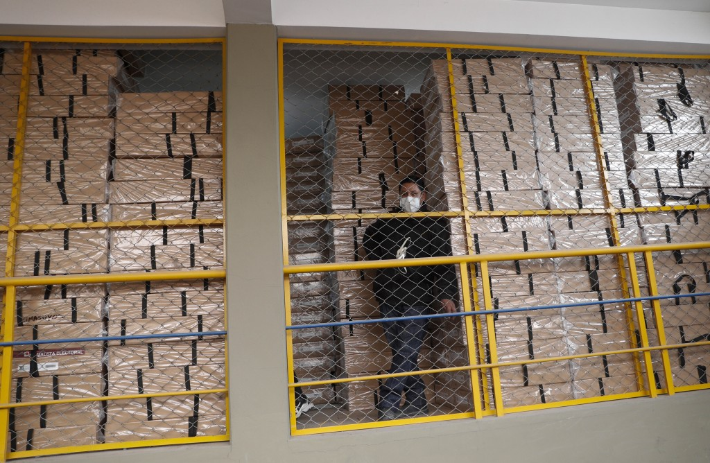 An electoral court worker stands next to election material at a distribution center in La Paz, Bolivia, Friday, Oct. 16, 2020. Bolivia will hold gener...