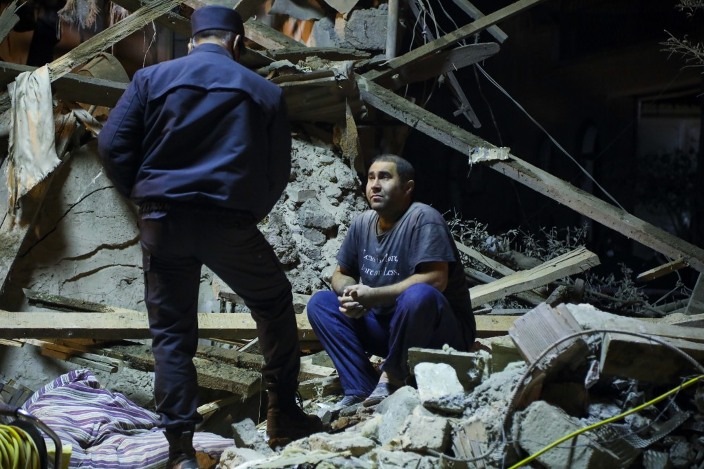 An Azerbaijan's policeman, left, speaks to a man siting at his destroyed house in a residential area that was hit by rocket fire overnight by Armenian...