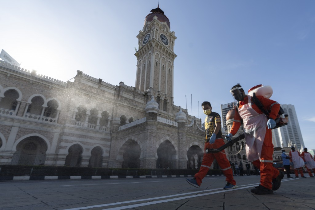 City hall workers spray a disinfectant at Merdeka Square, or independence square, situated in front of the Sultan Abdul Samad Building, background, in...