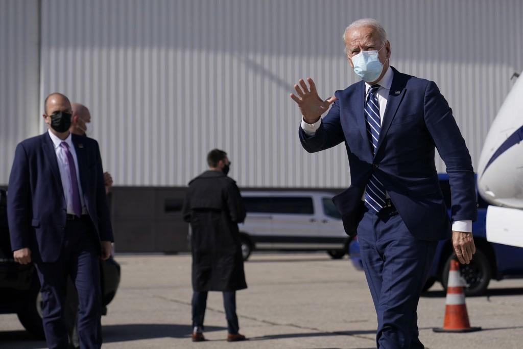 Democratic presidential candidate former Vice President Joe Biden waves as he arrives at Detroit Metropolitan Wayne County Airport, Friday, Oct. 16, 2...