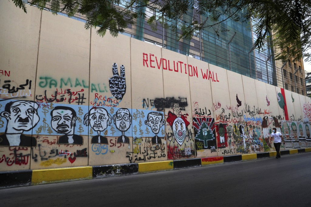 A man walks past the wall of United Nations Headquarters, decorated with graffitis painting in Beirut, Lebanon, Monday, Oct. 12, 2020. A year ago, hun...