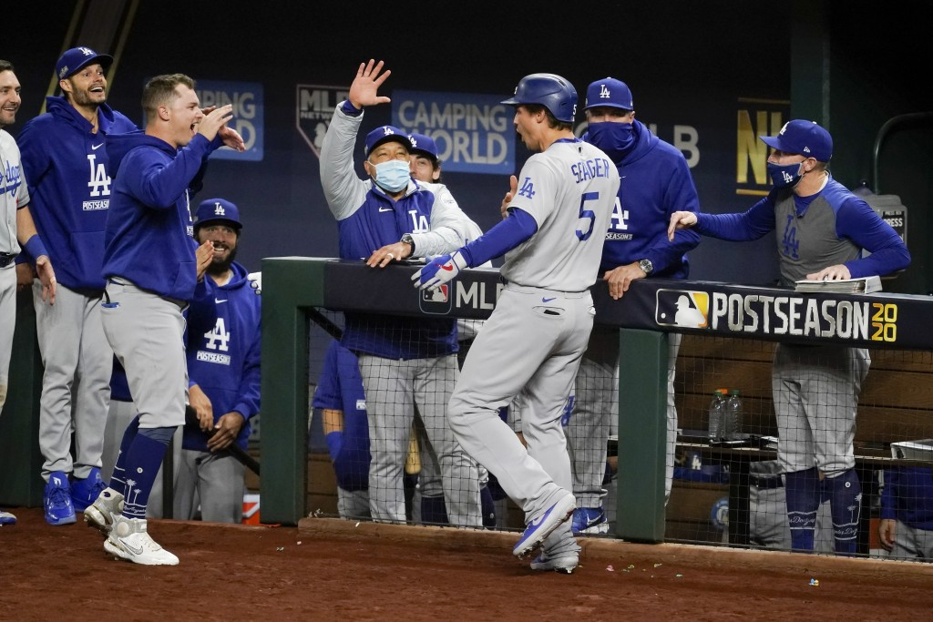 Los Angeles Dodgers' Corey Seager celebrates his two-run home run against the Atlanta Braves during the seventh inning in Game 5 of a baseball Nationa...
