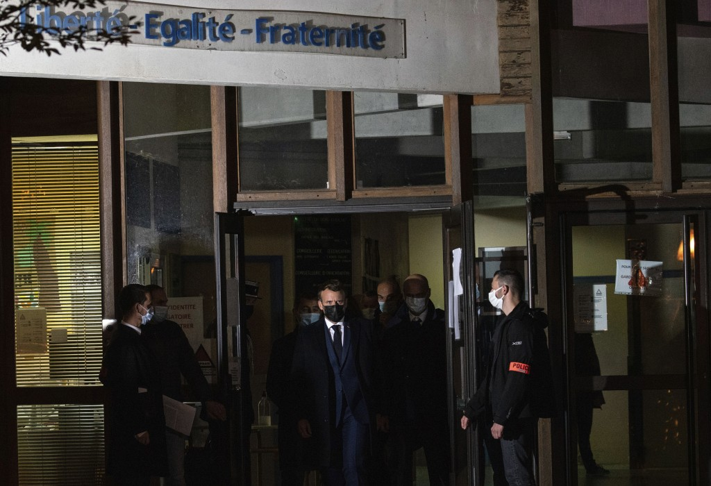 French President Emmanuel Macron leaves, center, a high school Friday Oct.16, 2020 in Conflans Sainte-Honorine, northwest of Paris, after a history te...