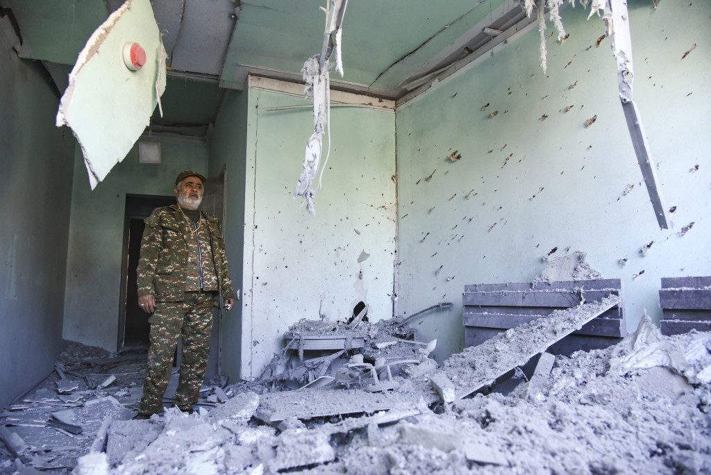 A man wearing a military uniform stands inside a house destroyed by shelling during a military conflict in Stepanakert in the separatist region of Nag...