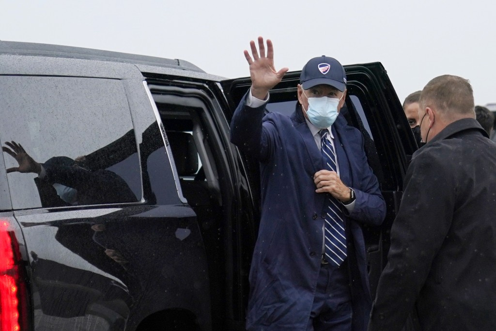 Democratic presidential candidate former Vice President Joe Biden waves as he exits his motorcade to board his campaign plane in New Castle, Del., Fri...