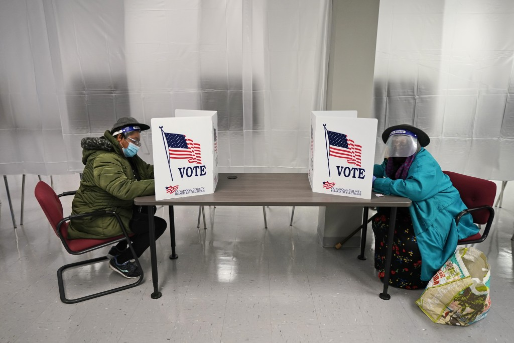 FILE - In this Oct. 6, 2020, file photo two voters fill out ballots during early voting at the Cuyahoga County Board of Elections in Cleveland. A surg...