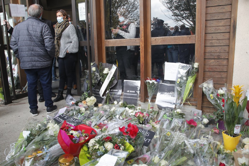 Flowers lay outside the school where slain history teacher Samuel Paty was working, Saturday, Oct. 17, 2020 in Conflans-Sainte-Honorine, northwest of ...