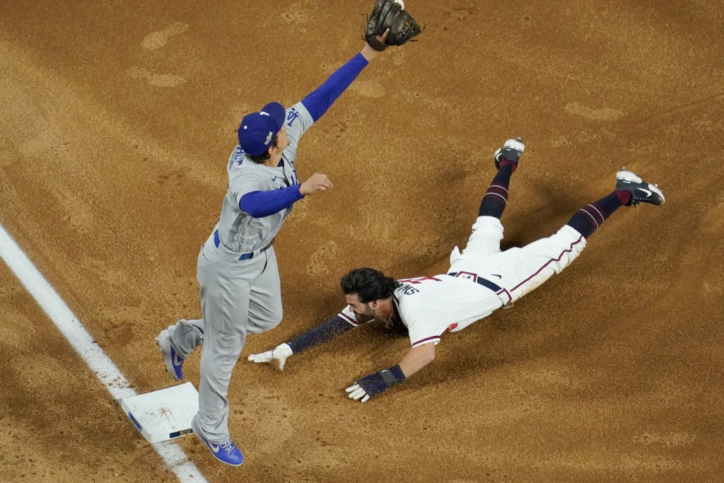 Atlanta Braves' Dansby Swanson is safe at third past Los Angeles Dodgers shortstop Corey Seager on a single by Nick Markakis during the second inning ...