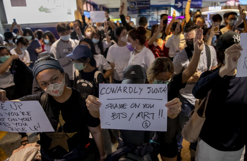 Pro-democracy protesters display placards against shutting down mass transport system at Ashok BTS station in Bangkok, Thailand, Saturday, Oct. 17, 20...