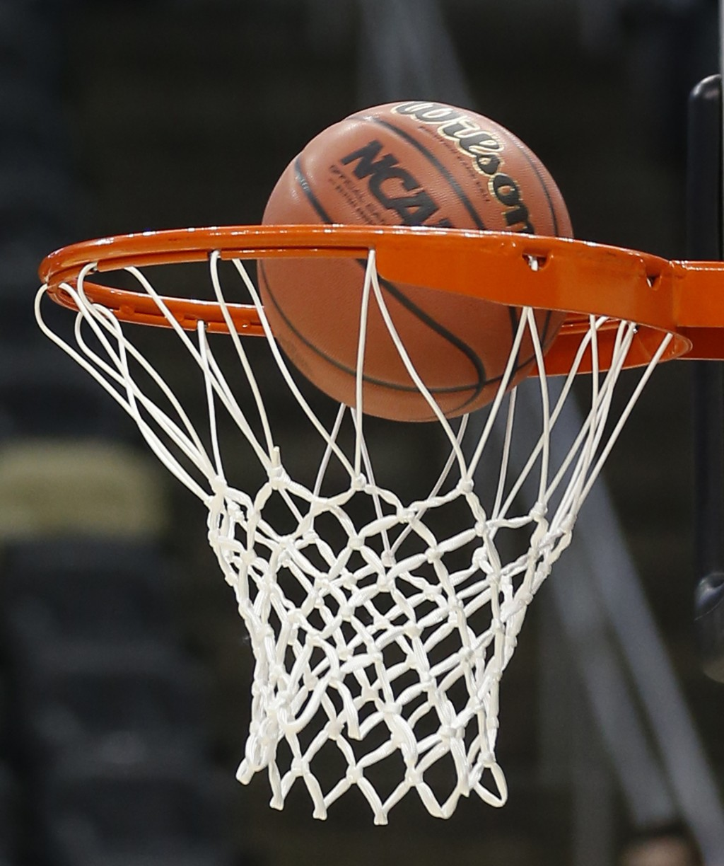 FILE - In this March 18, 2015, file photo, a basketball with the NCAA logo goes in on a shot by Northeastern during practice at the NCAA college baske...